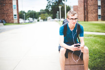 a college student sitting with his backpack listening to earbuds