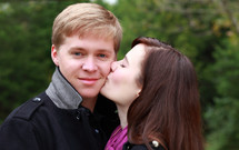girl kissing a boy on the cheek