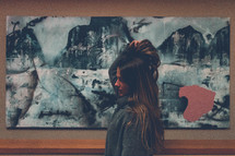 a woman standing in front of artwork on a wall