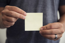 man holding a blank post-it note