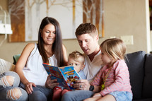 a family reading a children's book on the couch