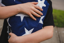 child carrying a folded flag