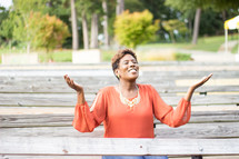a woman sitting on a bench with raised hands praising God