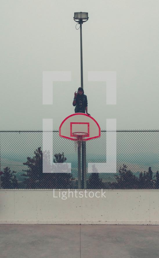 teen boy sitting on a basketball goal