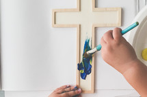 a toddler painting a cross with a stencil