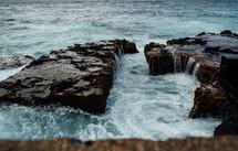ocean water washing over rocks