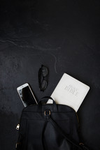 Bible, phone, and reading glasses in a backpack
