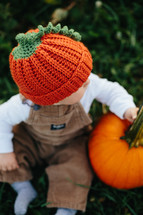 toddler in overhauls with a pumpkin
