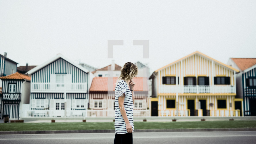 woman walking on a street in front of beach houses