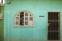 barred doors and window on mint green house