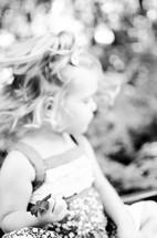 Toddler girl holding a flower in the park.