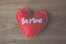 red felt heart with the words be mine