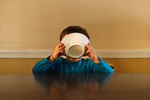a boy drinking milk out of a cereal bowl