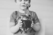 a boy holding a cactus in a mason jar