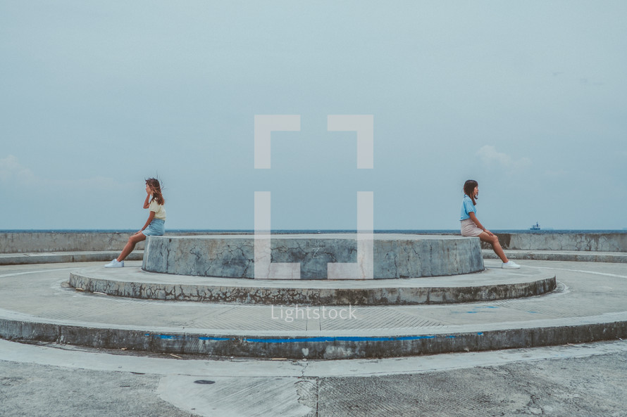 twins sitting on opposite sides on a concrete structure