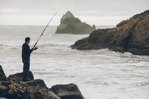 man standing on rocks fishing in the ocean