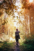 a woman backpacking on a path through a forest