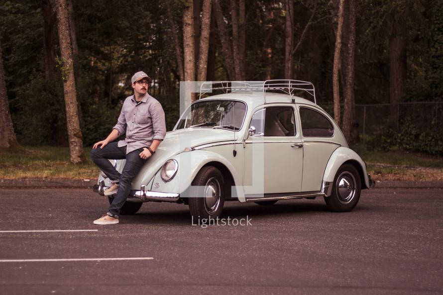 man leaning against a vintage Volkswagen Beetle