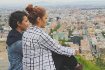 women taking in the view of a city below