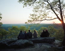 friends sitting at the edge of a cliff