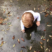 a toddler boy playing in a puddle