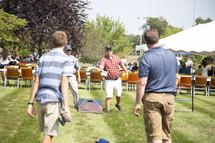 men and boys playing corn hole at a picnic