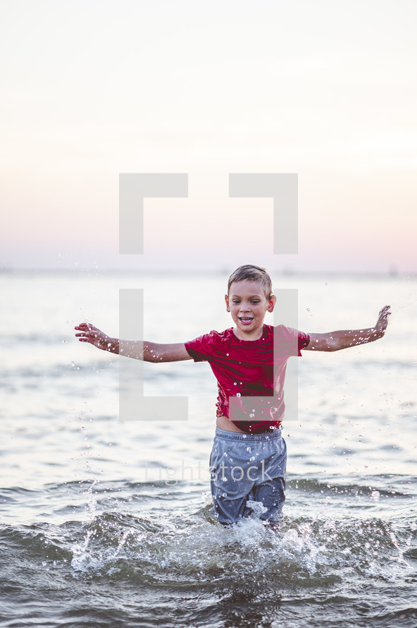 happy kid playing in the ocean