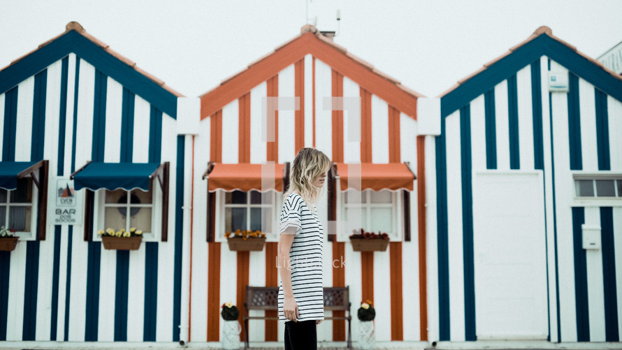 woman walking in front of striped beach houses