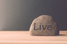 a rock with the word live