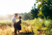 a couple standing in a field of tall grass in sunlight