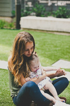 a mother with her infant daughter in her lap sitting in the grass