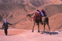 A man leading a camel through the desert