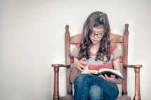 girl child sitting in a chair reading a Bible