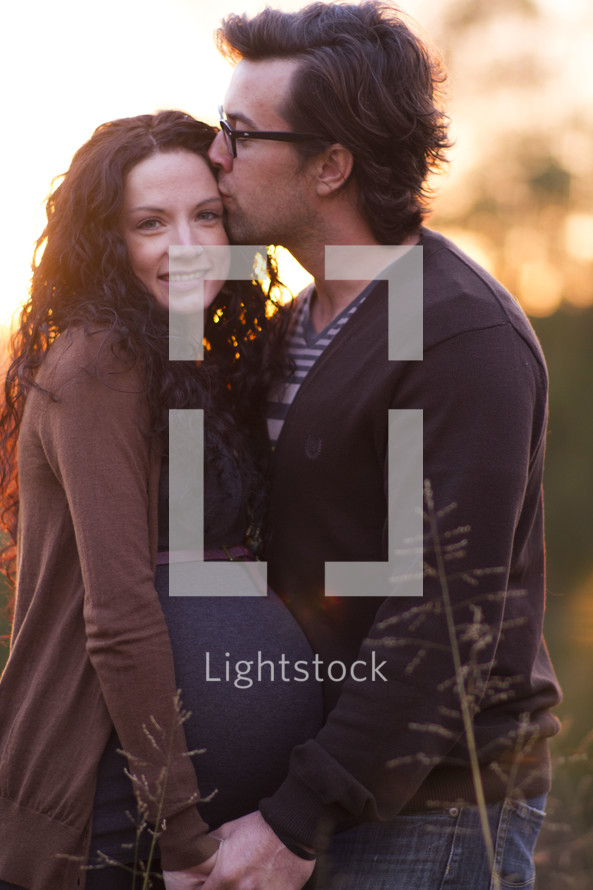 Expecting couple embracing outdoors at sunset.