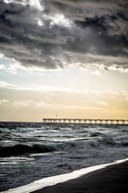 A long wooden pier extending into a stormy sea.