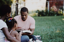 Family reading the Bible together outdoors.