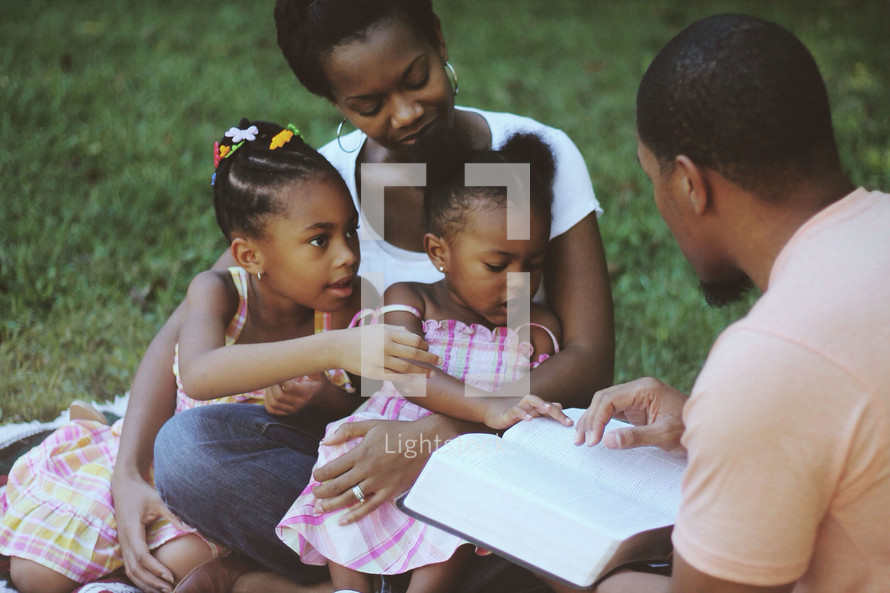 Family reading the Bible while sitting outdoors.