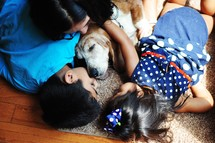 children sleeping on the floor with the dog