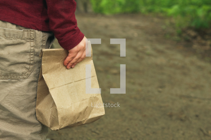 a child carrying a brown lunch bag