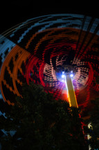 spinning light from a fair ride at night