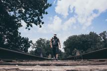 a man walking down a railroad track