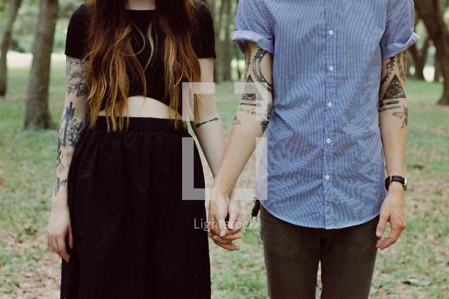 torso of a couple with tattoos holding hands