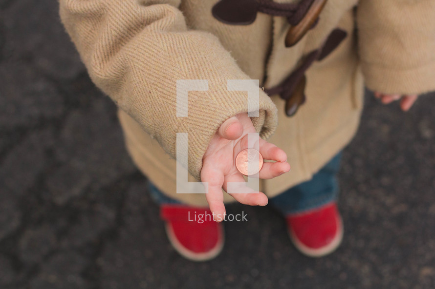 Child standing outside holding a penny.