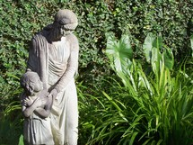 An image of a mother and child statue of a mother protecting her daughter from an unseen danger in the woods and wild.