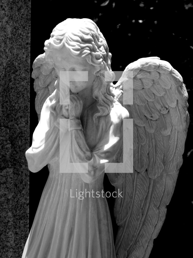 A statue of a female angel praying in black and white photography.