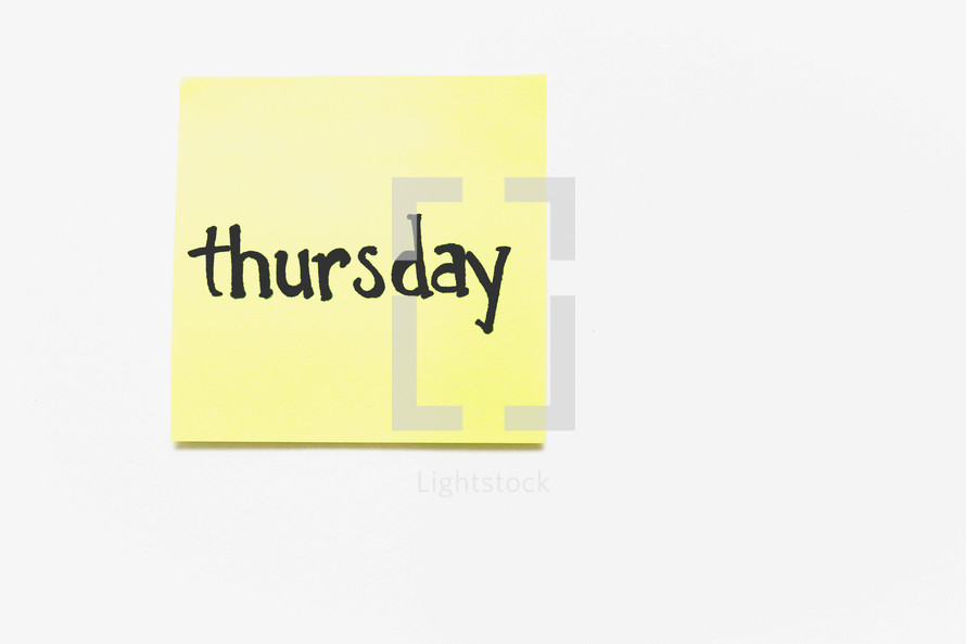 """A yellow sticky note with """"thursday"""" written in black ink."""