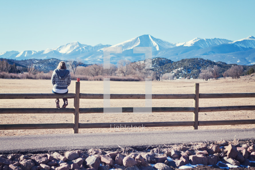 woman sitting on a fence looking out at a mountain