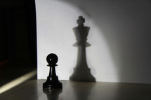 Light shining on a chess pawn, casting a shadow of a king chess piece.