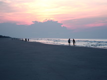 Silhouettes of people walking along the beach at sunrise.