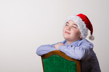Boy wearing a Santa hat sitting in a chair, smiling pleasantly with his chin up.